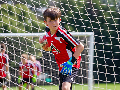 Goalkeeper rolling ball out from hands.
